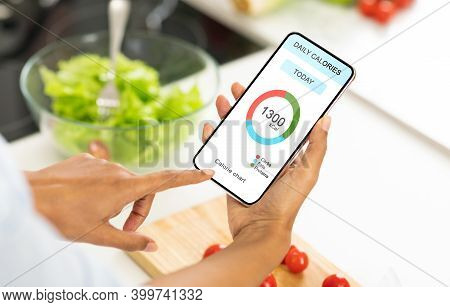Dieting Concept. Unrecognizable Woman Eating Vegetable Salad And Counting Daily Calories With App On
