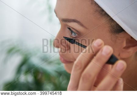 Closeup Of A Brunette Woman Applying Mascara At Her Lashes.