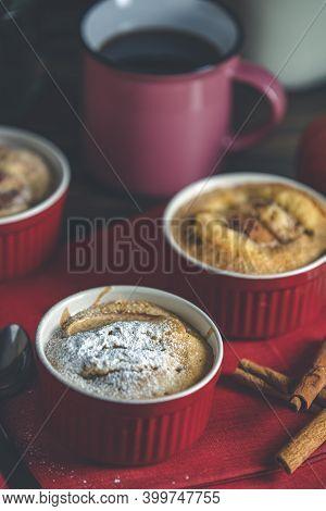 Three Apple Pies In Ceramic Baking Molds With Red Napkin Ramekin On Dark Wooden Table. Shallow Depth