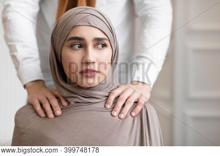 Domestic Violence And Abuse. Muslim Husband Touching Shoulders Of Scared Wife In Hijab Indoors. Unre