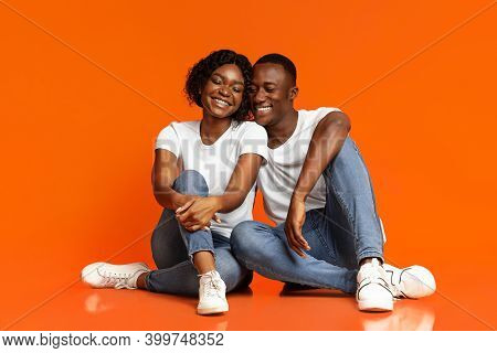 Loving Black Man And Woman Having Fun, Sitting On Floor And Laughing With Eyes Closed, Studio Shot,
