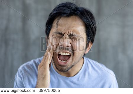 Young Asian Man Hands Pressed To Cheek As He Is Experiencing Severe Toothache On Gray Background