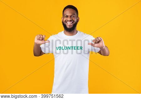 Im A Volunteer. Cheerful Black Activist Guy Pointing Fingers At Himself And Volunteer Inscription On