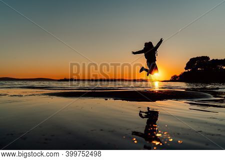 Silhouette Of Happy Joyful Woman Jumping And Having Fun At The Beach At Sunset/sunrise.freedom And H