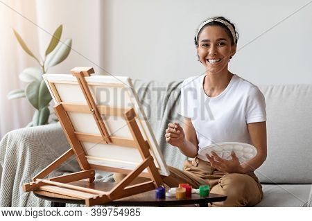 Happy Young Woman With Easel And Palette Painting At Home, Copy Space. Beautiful Lady Painting For H