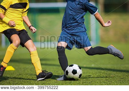 Two Soccer Players Compete In A Duel. Footballers Kicking Ball. Players In Yellow And Blue Shirts. S