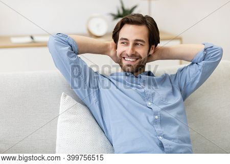 Smiling Man Relaxing Sitting On Couch At Home, Holding Hands Behind Head. Successful Millennial Guy