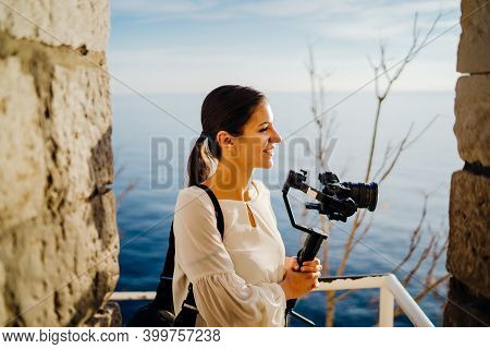 Smiling Female Travel Vlogger Video Creator Filming With A Mirrorless Camera On A Gimbal Stabilizer.
