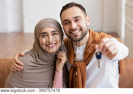 Own House. Cheerful Muslim Young Family Showing New Home Key Smiling To Camera Sitting On Sofa In Ow
