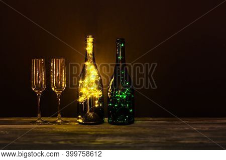 Festive Romantic Postcard. Shining Champagne Wineglasses, Wooden Table On Dark Background. Cozy Stil