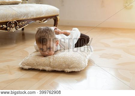A Young Boy Is Indulging On The Floor. Lies On A Pillow.