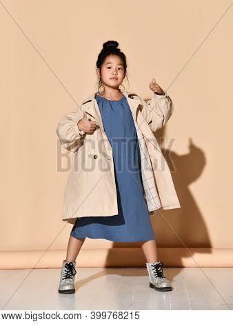 Little Korean Brunette Girl Dressed In A Blue Dress, Beige Trench Coat And Boots Raises Her Thumbs U