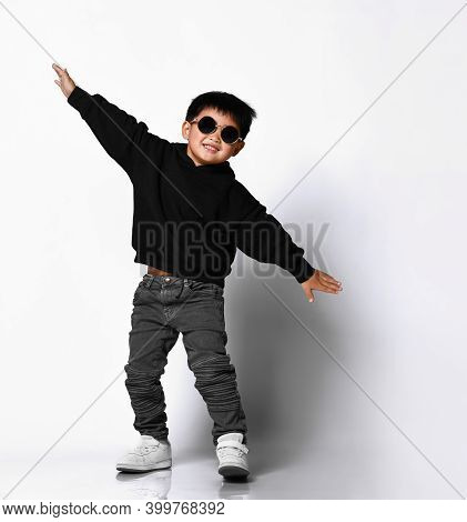 Portrait Of A Cute Little Boy In Stylish Clothes And Sunglasses Spreading His Arms And Having Fun Ne