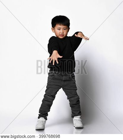 Cool Korean Little Boy Dressed In A Stylish Black Hoodie And Jeans Posing In The Studio On A White B
