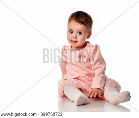 Cute Baby Girl Sits On A White Background. Adorable Little Kid Looking At The Camera. The Studio Sho