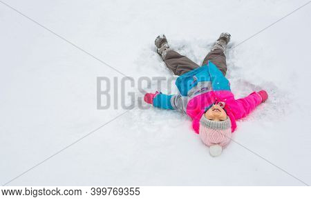 A Child Lies In The White Snow In In A Bright-colored Jacket And Makes The Trail Of An Angel