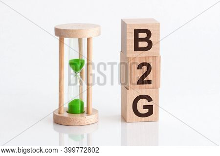 Close-up Of An Hourglass Next To Wooden Blocks With The Text B2g. B2g - Business-to-government
