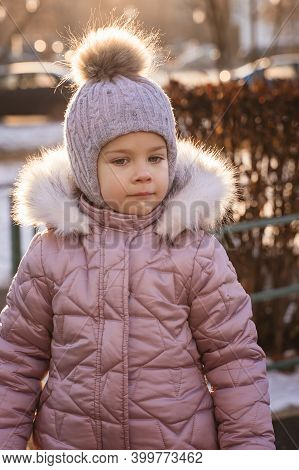 Cute Little Girl 4-5 Years Old In A Knitted Hat And Warm Jacket On A Walk On A Sunny Winter Day. Bac