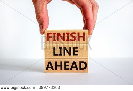 Finish Line Ahead Symbol. Male Hand Builds Stack From Blocks With Words 'finish Line Ahead'. White T