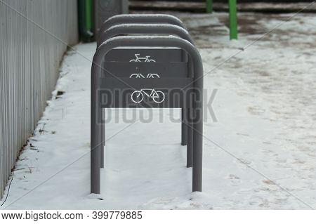 Urban Street Gray Metal Bike Rack With White Bike Badge On Winter Urban Background. Green Transport