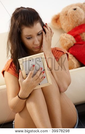 Heart-broken young girl looking at ex-boyfriends photo crying.