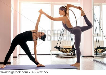 Two Attractive Young Women Balancing And Practicing Yoga In A Light Studio. Well Being, Wellness Con