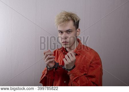 a teenager in handcuffs on a gray background. juvenile delinquent, criminal liability of minors. Mem