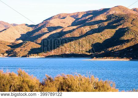 Rural Field Covered With Chaparral Plants Surrounding Barren Mountains During Sunset Creating Natura