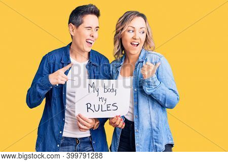 Couple of women holding my body my rules banner pointing thumb up to the side smiling happy with open mouth