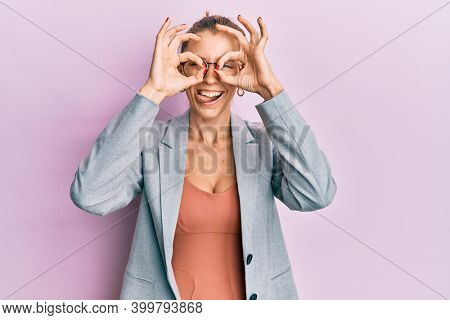 Beautiful caucasian woman wearing business jacket and glasses doing ok gesture like binoculars sticking tongue out, eyes looking through fingers. crazy expression.