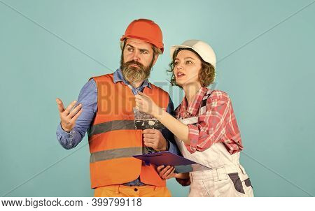 Plastering Works. Couple Look Documents. Woman And Man Safety Hard Hat. Couple Planning Changes Reno