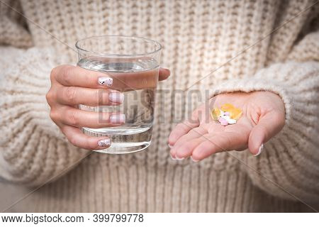 Woman Hands Holding Glass Of Water, Vitamins And Supplements. B12, D3, Selenium. Vitamins For Vegans