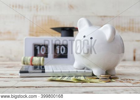 Piggy Bank, Calculator And Money On Wooden Table. Tuition Fees Concept