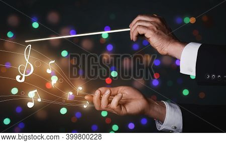 Hands Of Male Conductor On Dark Background With Blurred Lights
