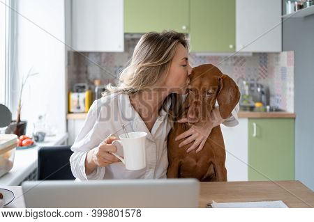 Woman In Sleepwear Kissing And Hugging Her Beloved Wirehaired Vizsla Dog, Sitting On The Chair In Ki