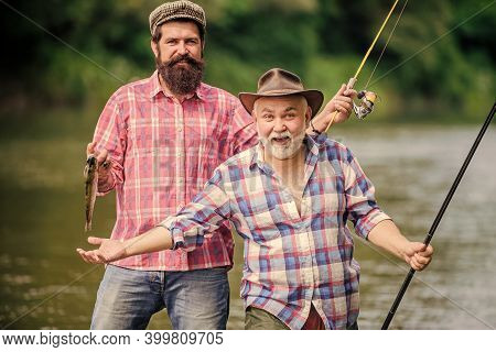 Sunny Summer Day At River. Fishing Peaceful Activity. Father And Son Fishing. Grandpa And Mature Man