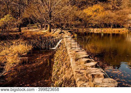 Rock Footbridge Across Small Lake On Autumn Morning.