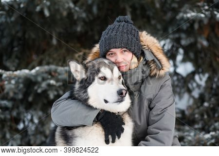 Alaskan Malamute Hugging With Woman In Winter Forest. Close Up.