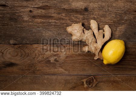 Close Up Of Fresh Ginger Root And Lemon On Wooden Table