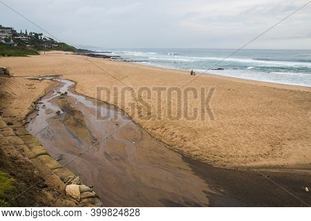 Stream Running Onto Beach With Waves And Rocks In Background