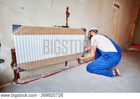 Male Plumber In Work Overalls Installing Heating Radiator In Empty Room. Young Man In Safety Helmet