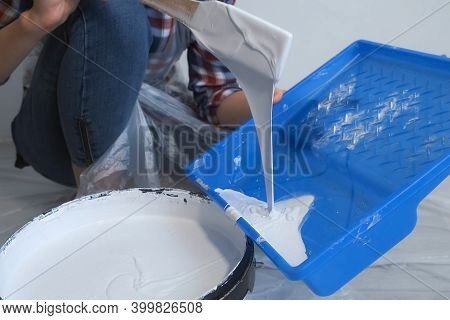 Woman Painter Is Pouring Paint In A Tray For Painting Walls Using Wooden Spatula, Closeup View. Diy