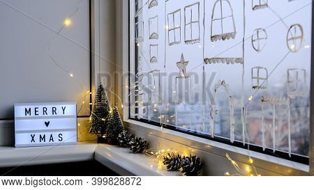 Lightbox With Text Merry Xmas Christmas On Windowsill. New Year Decorations, Garland Lights And Chri