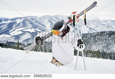 Alpine Skier In Snowboard Jacket Holding Skis And Ski Poles While Trying To Walk Through Deep White