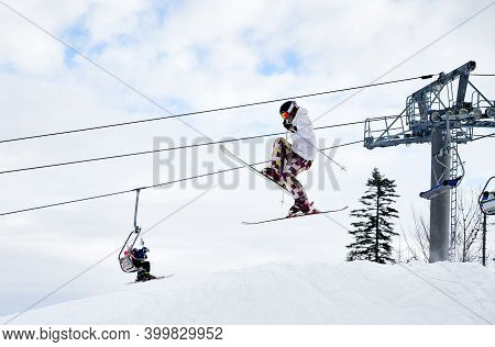 Side View Of Man Skier Making Jump In The Air With Cloudy Sky And Ski Lifts On Background. Male Free