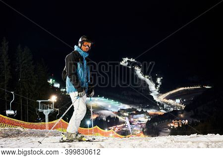 Male Skier In Winter Ski Jacket And Helmet Holding Ski Poles. Young Man Standing On Snow-covered Slo