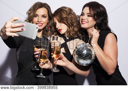 Three fashionable young women dressed in black cocktail dresses are singing with a microphone, holding disco balls, glasses of champagne