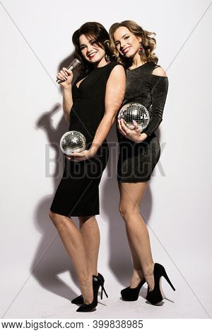 Two charming ladies dressed in black cocktail dresses sing songs from a microphone, hold disco balls and smile, dance.