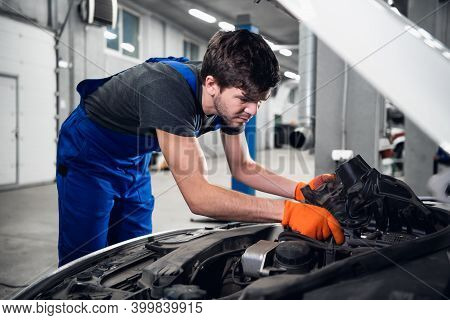 Repairman Is Fixing A Car Engine. He Is Dressed In Overalls And Gloves