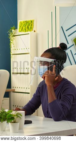 African Entrepreneur With Protective Mask And Visor Making Telephone Financial Negotiations While Co